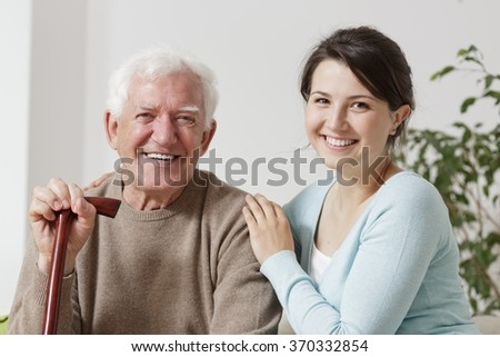 Adult daughter is hugging her old father - stock photo