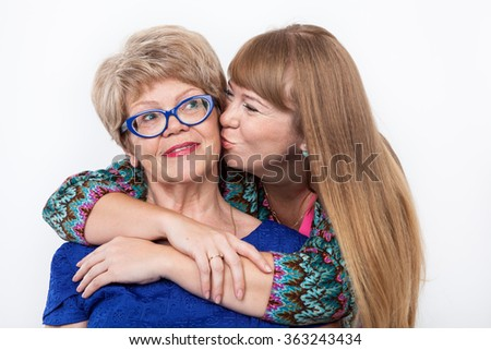 Adult daughter kissing her senior mother, smiling faces looking at camera, on white background - stock photo