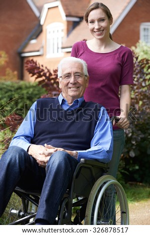 Adult Daughter Pushing Father In Wheelchair