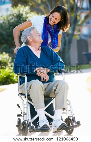 Adult Daughter Pushing Senior Father In Wheelchair - stock photo