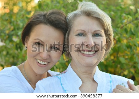 adult daughter walking in autumn park with her mother