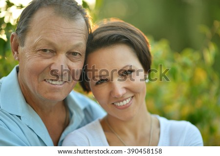 adult daughter walking with an elderly father in the autumn park - stock photo