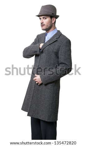 Adult dressed in a gray overcoat and a gray hat, very serious, with an intimidating expression, reaching with his hand to the overcoat's inner pocket. Isolated on white background. - stock photo