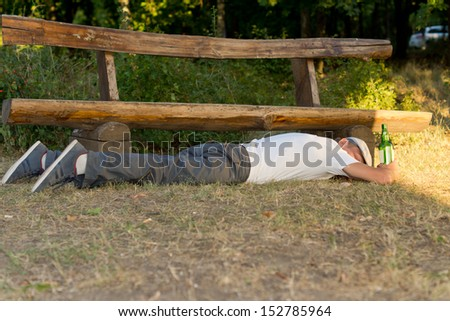Adult drunk man sleeping down on the ground next to a bottle of alcoholic drink in the park - stock photo