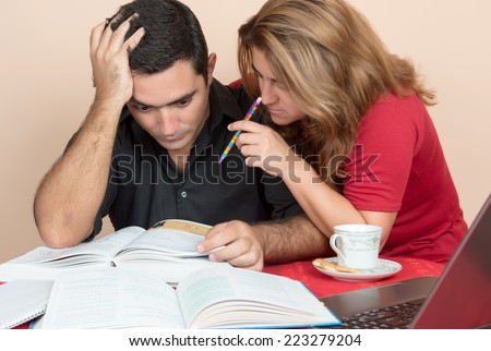 Adult education - Hispanic man and woman studying or doing office work at home - stock photo