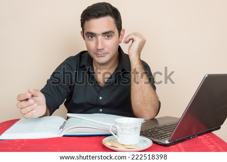 Adult education - Hispanic man studying or working at home - stock photo