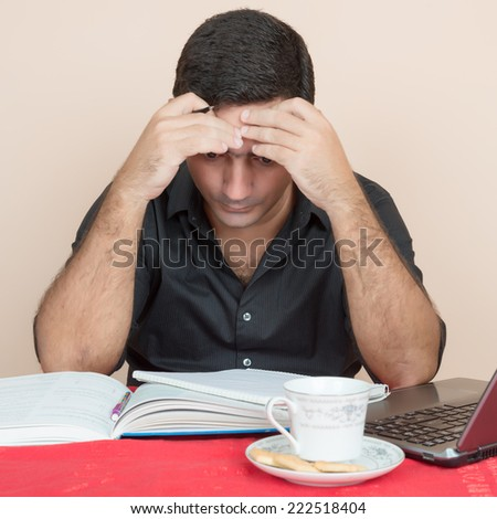 Adult education - Tired hispanic man studying at home - stock photo