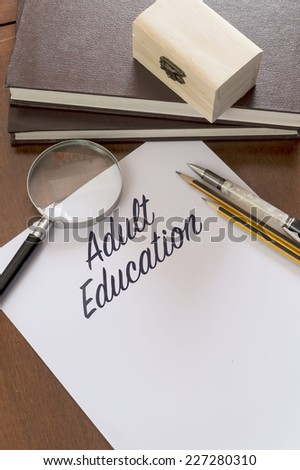 Adult education word on paper - stock photo