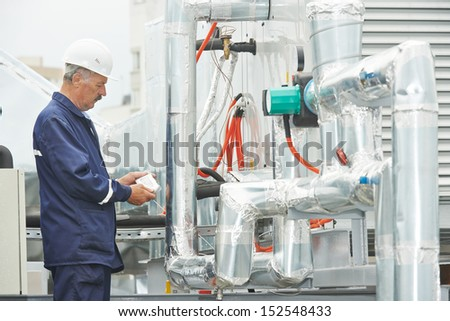 adult electrician engineer working with ventilation and conditioning system