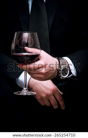 adult elegant man hold glass of red wine, close up, indoor shot, selective focus - stock photo