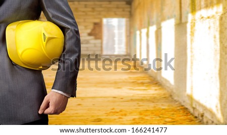 adult engineer or inspector hand holding yellow plastic helmet for workers security over big empty space room with window in perspective and door background No face Copy space for inscription