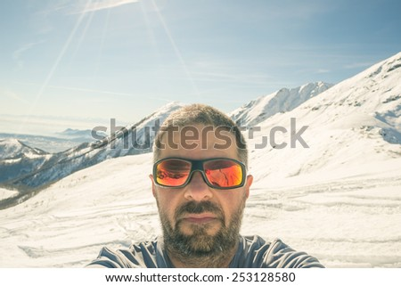Adult european man taking selfie on snowy slope in ski resort with the beautiful snowcapped italian Alps in the background. Shot in backlight with clear sky. Toned image, old retro touch, desaturated. - stock photo