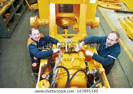 adult experienced industrial workers during heavy industry machinery assembling on production line manufacturing workshop - stock photo
