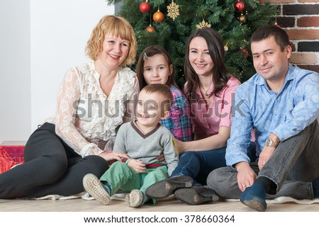 Adult family with three young children sit near New Year Christmas tree - stock photo
