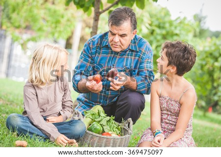 Adult Farmer with Children and Harvested Vegetables,Italy