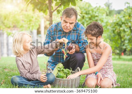 Adult Farmer with Children and Harvested Vegetables,Italy - stock photo