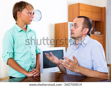 Adult father and teenage son discussing something interesting indoors - stock photo