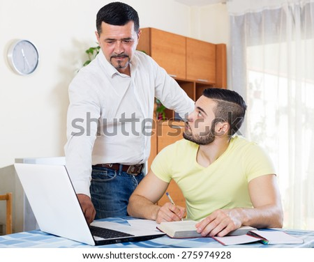 Adult father helping adult son to do homework. Focus on the right man - stock photo