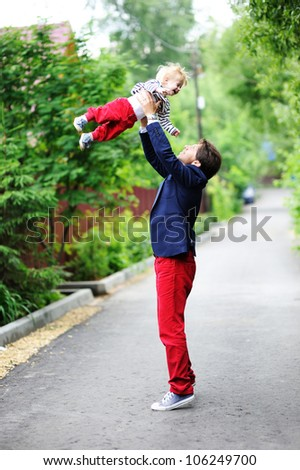 Adult father playing with little child boy in the park - stock photo