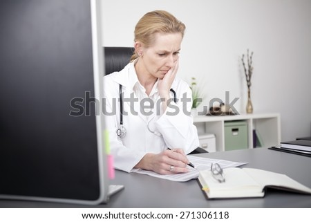 Adult Female Clinician Sitting at her Office and Reading Medical Reports Seriously While Leaning on her One Hand. - stock photo