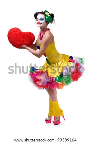 Adult female clown holding red heart - stock photo