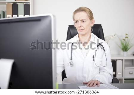 Adult Female Doctor with Stethoscope on her Shoulders Looking at the Computer Monitor Seriously While Sitting at her Working Table. - stock photo