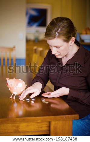 Adult female emptying money out of Toy money box, sitting at Kitchen table - stock photo