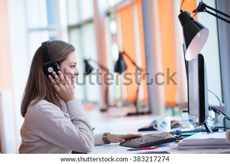 Adult female secretary with headphones doing customer service in a callcenter - stock photo