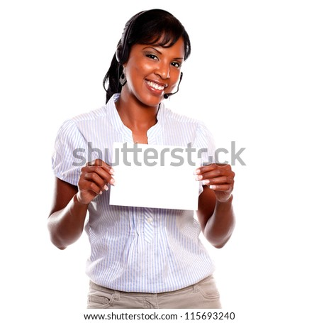 Adult female wearing headphones looking at you and holding white card on isolated background - copyspace - stock photo