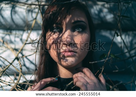 adult female with short hair shadows on face caught in vines