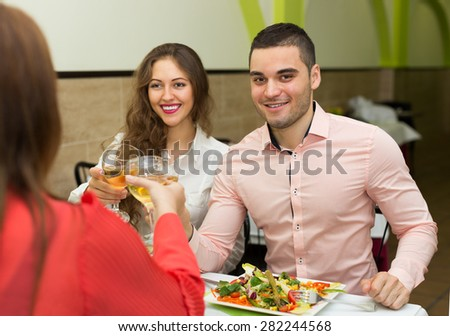 Adult friends having dinner together in modern cafe