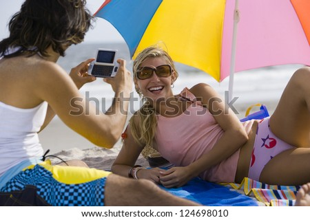 Adult friends making photos on the beach while sunbathing - stock photo