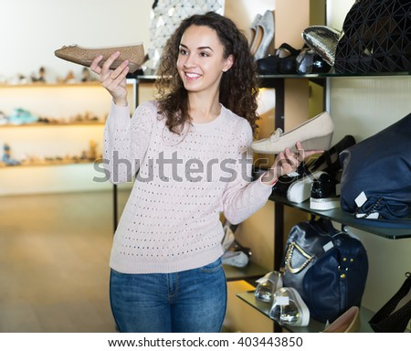 Adult girl chooses summer shoes at fashionable shop