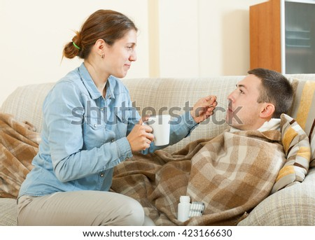 Adult girl giving giving drugs to diseased man at home - stock photo