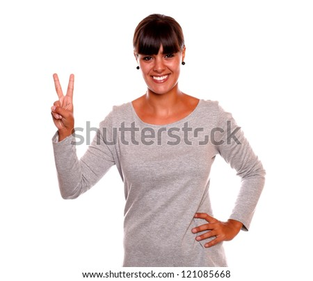 Adult girl holding up two fingers in victory sign on grey dress standing over white background - stock photo