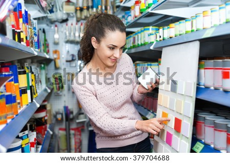 Adult girl selecting paints for interior in household store - stock photo