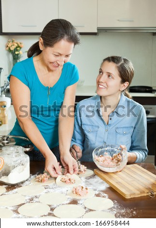 Adult girl with mature  mother making  dumplings from stuffing and dough