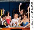 adult group celebrating friend winning blackjack - stock photo