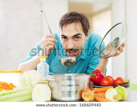 Adult guy tasting  vegetarian soup with ladle  - stock photo