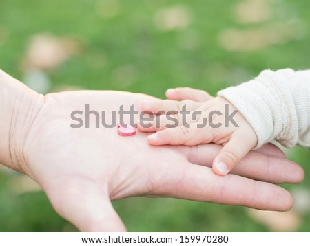 adult hand holding a child's hand with a wooden heart - stock photo