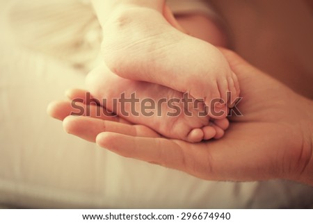 Adult hand holding baby feet, closeup