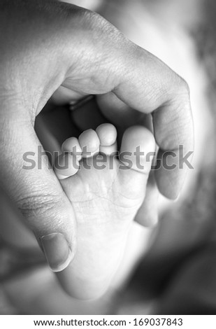 Adult hand holding baby's foot