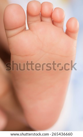 Adult hand holding the child's feet.
