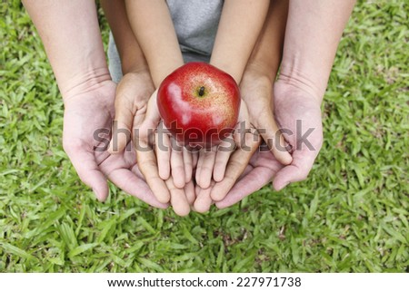Adult hands holding kid hands with red apple on top  - stock photo