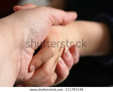 adult holding firming to a child's hand