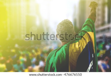 Adult holding the flag of Brazil in Paulista Avenue
