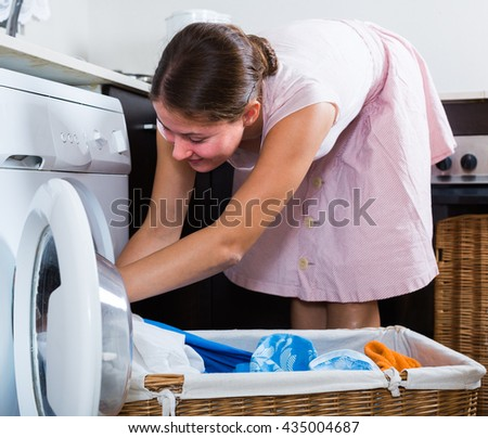 adult housewife with basket of linen near washing machine indoors