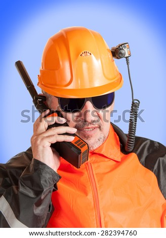 Adult industrial worker in orange uniform and blue glasses, with helmet camera, talking on radio transceiver.  - stock photo