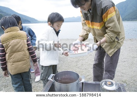 adult male and three boys making curry by lakeside