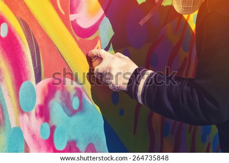 Adult Male Graffiti Artist Paint Spraying the Wall, Urban Outdoors Street Art Concept, Toned Image with Selective Focus - stock photo